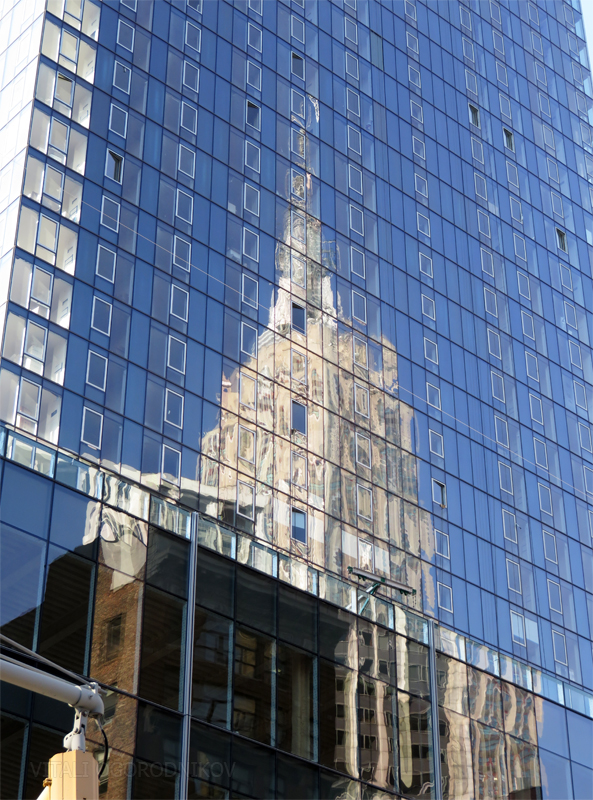 The Empire State Building is reflected in the façade