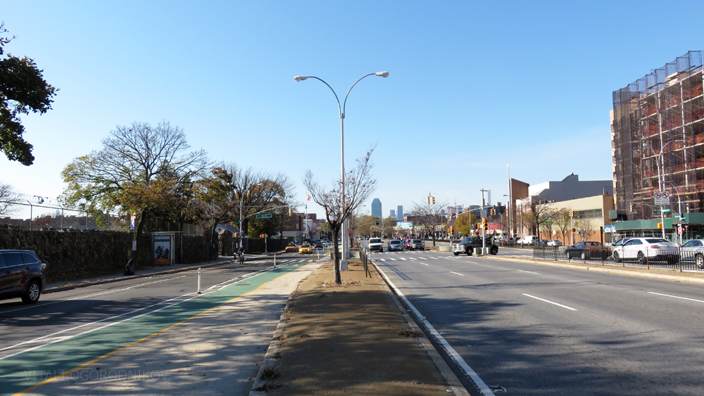 Underused median on the south side of Queens Boulevard, with the cemetery to the left and the neighborhood to the right