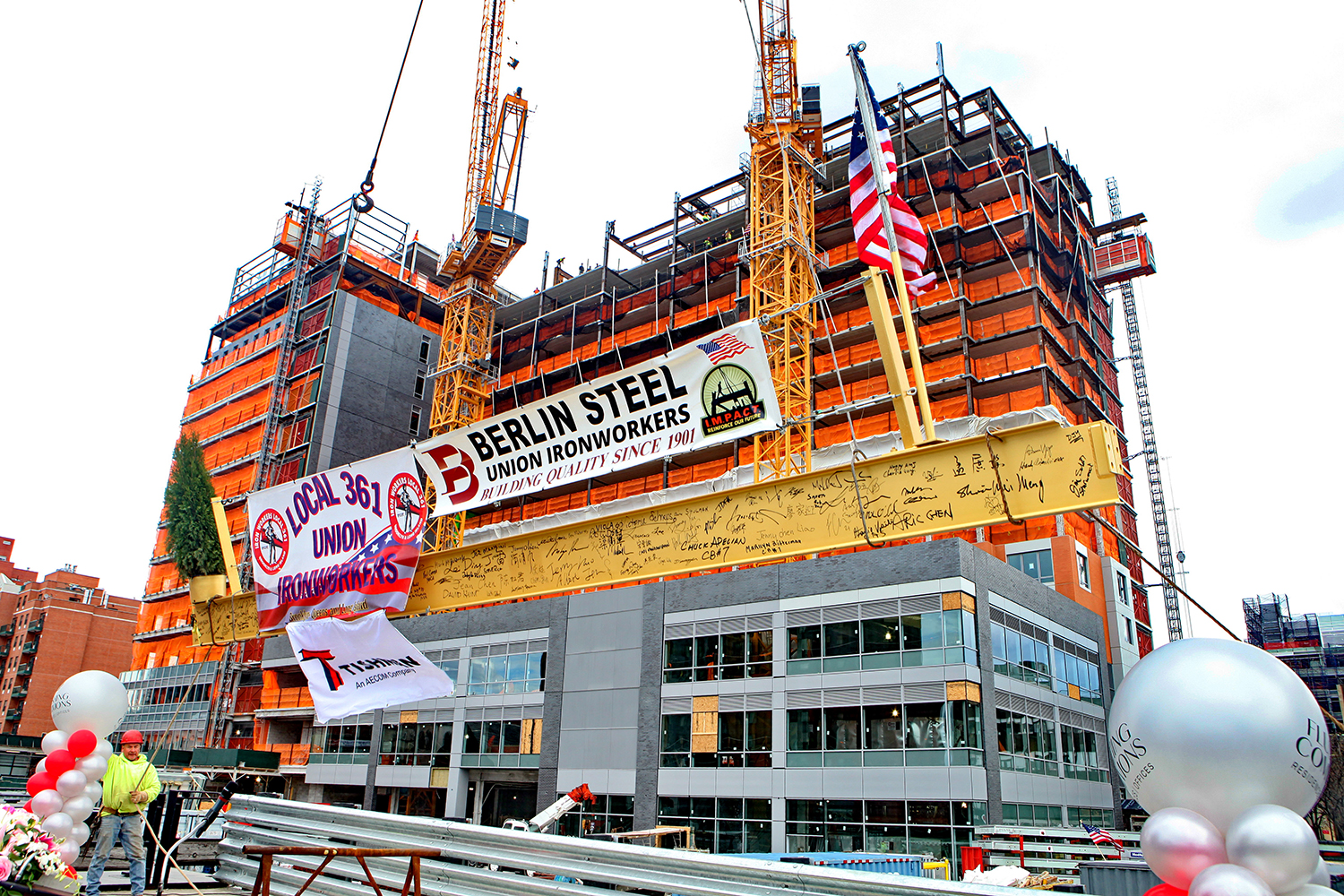 The topping out beam is raised into place at 138-35 39th Avenue at Flushing Commons. Credit: F&T Group