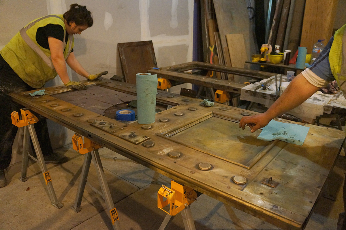 Restorers from Ferrous Research and Design polish a steel elevator door.