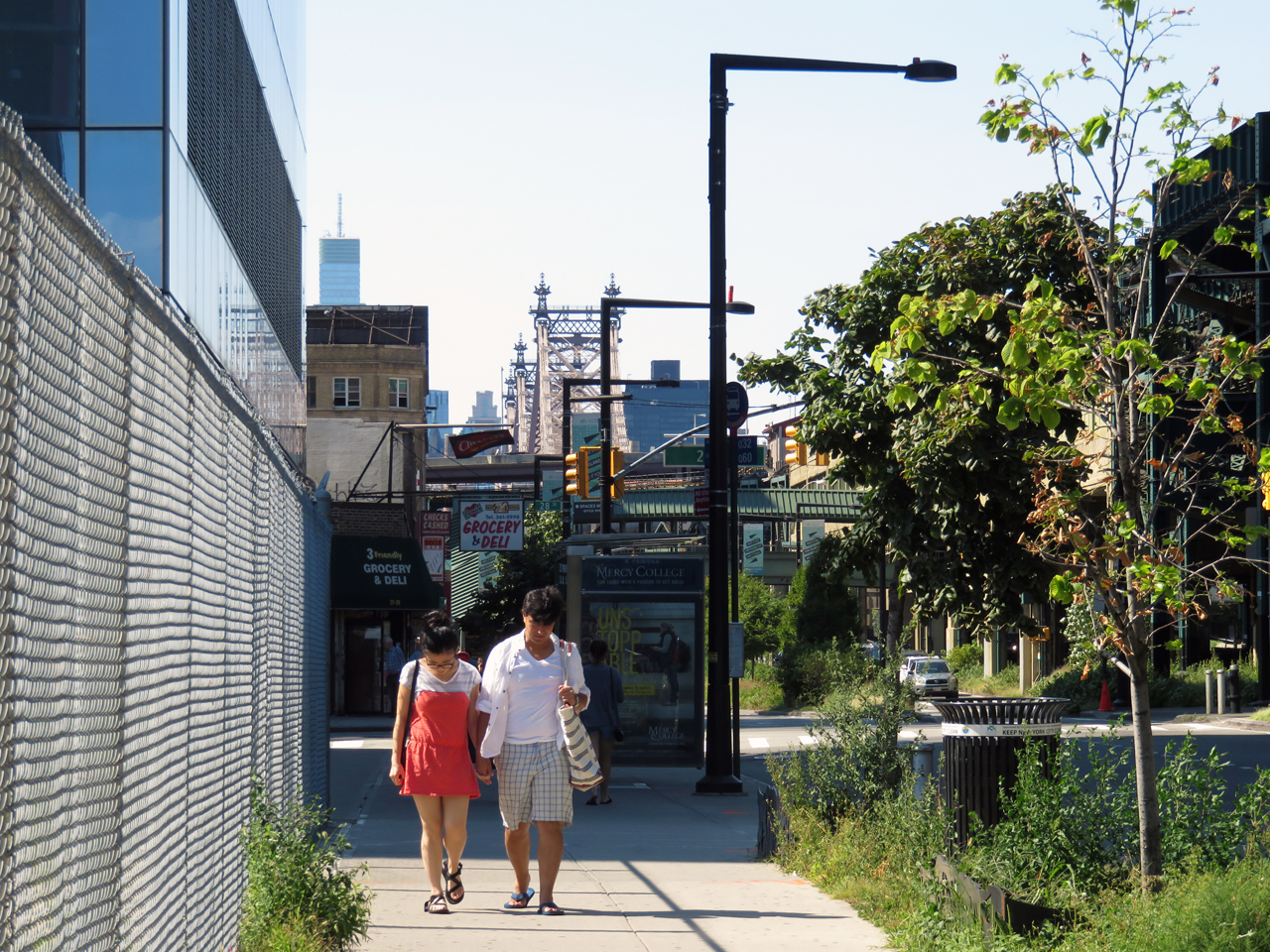 Queensboro Plaza (in the distance), as seen along Queens Plaza South from the site of 28-07 Jackson Avenue (fence on the left)