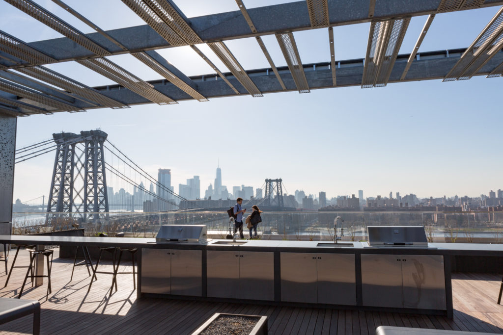 Rooftop terrace and grill at 325 Kent Avenue with Downtown Manhattan in the distance, image by Andrew Campbell Nelson